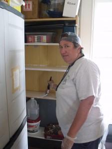 Carolyn Dodson paints shelves in equipment room.