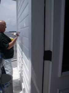 Joan Spiece  paints siding board replaced earlier in the day.