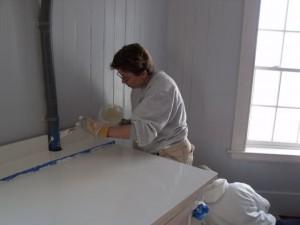 Photo by Tony Pasek Cory Talbott paints battery cabinet in kitchen.