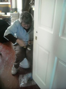 Photo by Hobie Statzer. Virginia works on door.