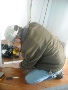 Photo by Hobie Statzer.  Andy Grey working on kitchen floor.
