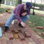 Photo by Tony Pasek. Hobie installs memorial bricks on walkway.