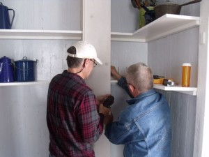 Photo by Tony Pasek: Andy and Hobie work on kitchen pantry.