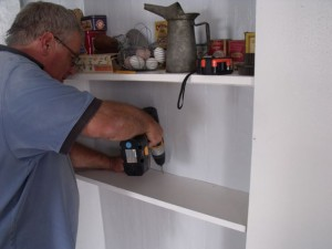 Photo by Tony Pasek Steve Von Briessen installs third shelf in pantry.