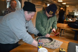 Dick Moale and Lightship Volunteer Stephanie Senkevich work on porthole.