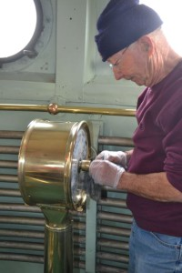 Dick Moale polishing brass in pilot house.