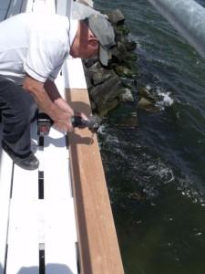 Hobie installing deck board.