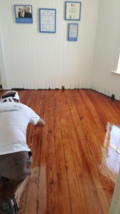 Henry applies varnish to the recently sanded floor.