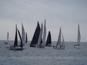 Plenty of sailboats participating in a race near the lighthouse