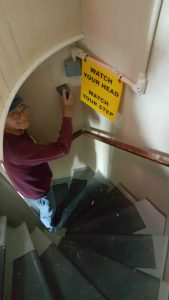 Tony sanding the stairwell wall.