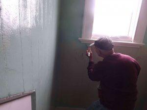 Dick paints window sill in dormer.
