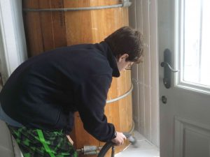 Val vacuums dust from around water tank.
