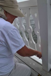 Mary caulking railings on main deck.