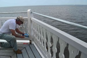 Steve caulks railings on main deck.