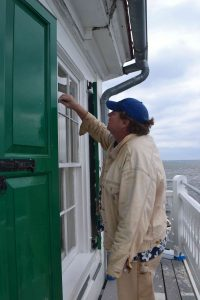 James Stein removes painters tape after painting window frames.