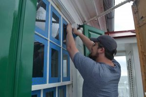 Sean Goodison removing tape after painting window frames.