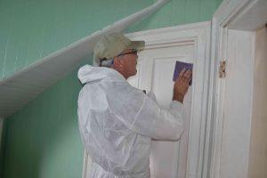 Steve Blakely sanding door before it is repainted.