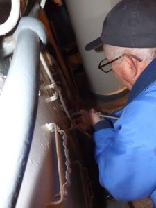 Hobie feeds wire down to Engine Room