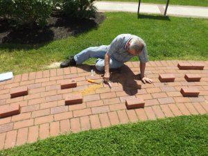 Hobie Statzer inserting memorial bricks in Concord Point walkway.