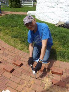 Tony Pasek inserting bricks in Concord Point walkway.
