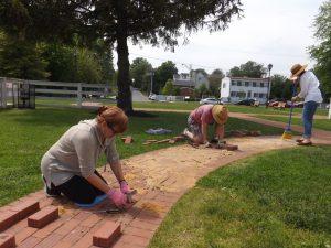 Friends volunteers (from Left) - Barbara, John & Bethany help install the new bricks.