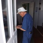 Bob Stevenson works on kitchen door.