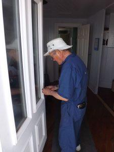 Bob Stevenson works on kitchen door.