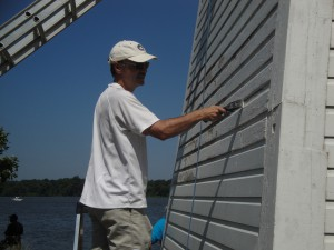 Volunteer Andy Gray applies a coat of paint to Fort Washington Light.