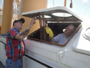 Photo by Anne Puppa Hobie and Ed prime the hatch after screen was removed.