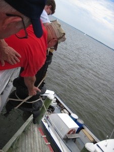 Photo by Tony Pasek We Got It! Tom Lorenzen & Al Pearson lift the 80 pound stove up under Hobie's supervision