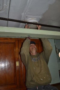 Photo by Anne Puppa Tony putting cover back on light in wardroom.