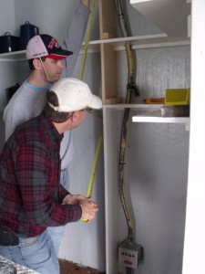 Photo by Tony Pasek: Andy and Karl work on kitchen pantry.
