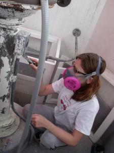 Photo by Tony Pasek: Claudia Talbott scrapes pedestal.
