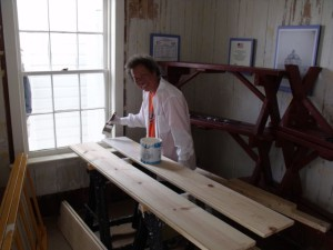 Photo by Tony Pasek: Susie Jablonskie paints new baseboards for sitting room