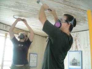 Photo by Hobie Statzer. Keast & Hood volunteers scrape flaking paint from ceiling.