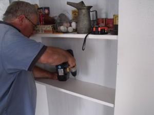 Photo by Tony Pasek Steve Von Briessen installs third shelf in pantry.
