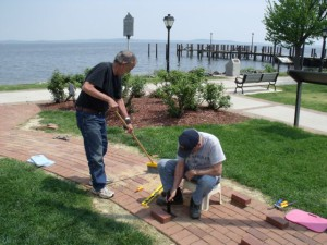 Friends of Concord Point LH president Floyd Dobson helps Hobie with brick placements.