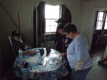 Winnie, Alma & Hobie look over last Point Lookout Light station's keeper Ray Hartzell's photo album.