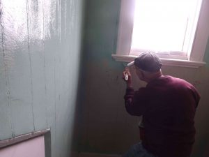 Dick paints window sill in dormer.