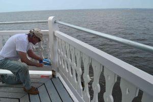 Steve caulks railings on main deck.