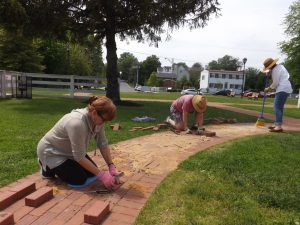 Friends volunteers (from Left) - Barbara, John & Bethany help install the new bricks.