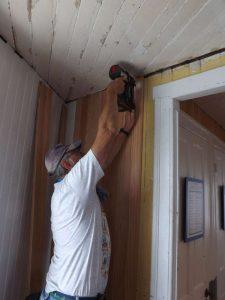 Tony installs siding in equipment room.