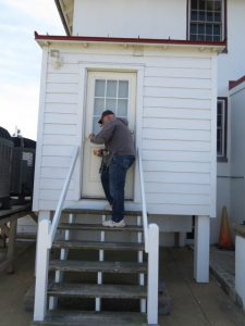 Gerry touching up paint on keeper's house.