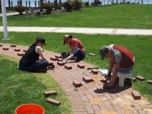 Jessica Lapota and Bethany Baker of the Friends group assist Hobie install new Legacy bricks in lighthouse walkway.