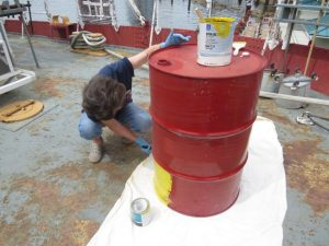 Donna painting safety barrel